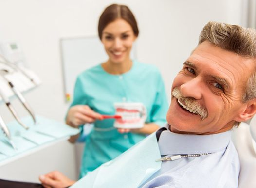 older man smiling in dental chair with hygienist