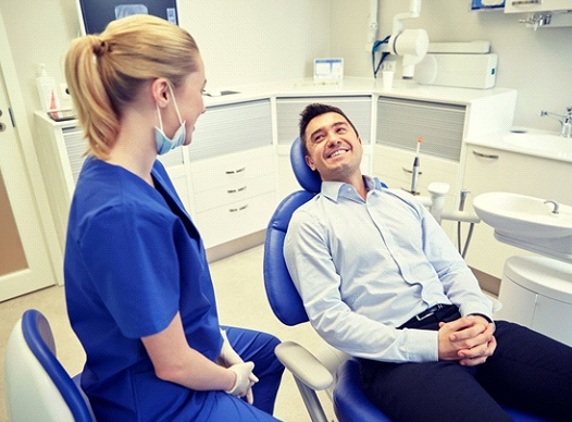 man sitting in dental chair and smiling at his dentist