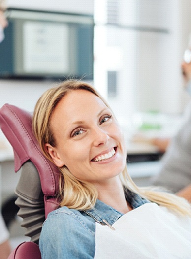 young woman smiling in the dentist chair after having a smile makeover