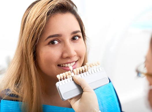 A young woman looking at the camera while a dentist uses a shade guide