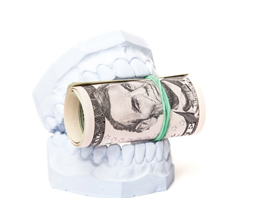 A white mouth mold holding a rolled-up wad of bills bound with a rubber band