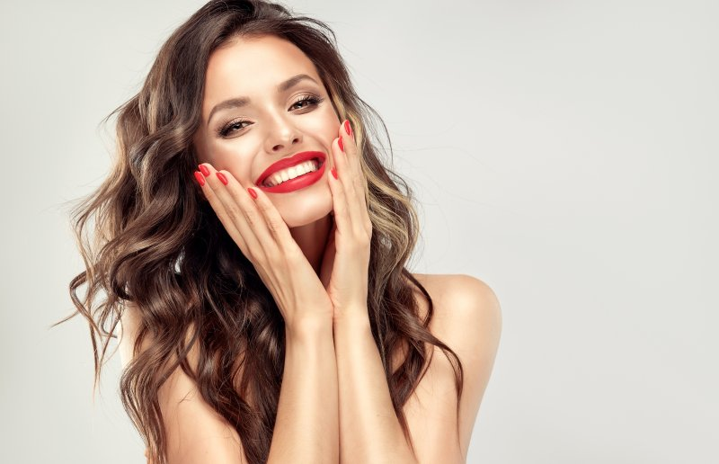 a young woman with brown wavy hair and red lipstick holding her face to show off her smile makeover