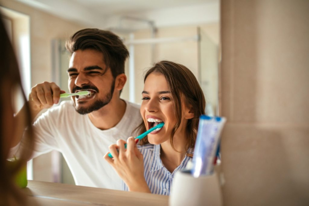 Man and woman brushing their teeth with tips from the dentist