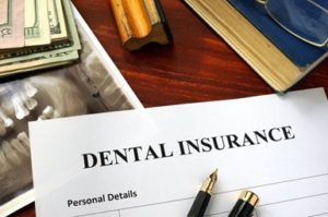 Dental insurance form sitting on a desk surrounded by a dental X-ray, a pen, a stack of money and an ink stamp.