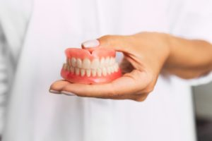 dentist holding set of dentures in Moses Lake
