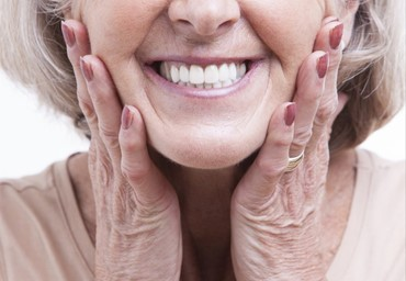 Woman smiling with her hands on her cheeks