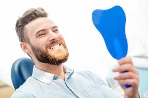 Man looking in mirror at cosmetic dentist